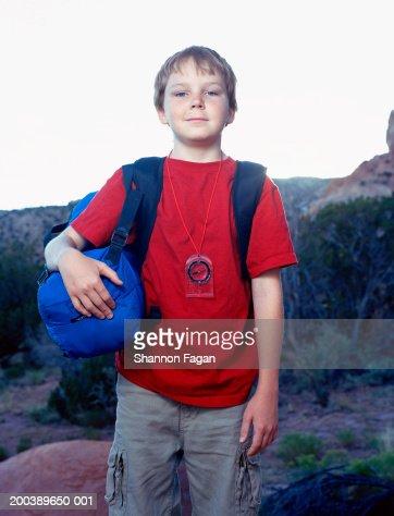 Boy (11-13) wearing compass, carrying duffel, portrait