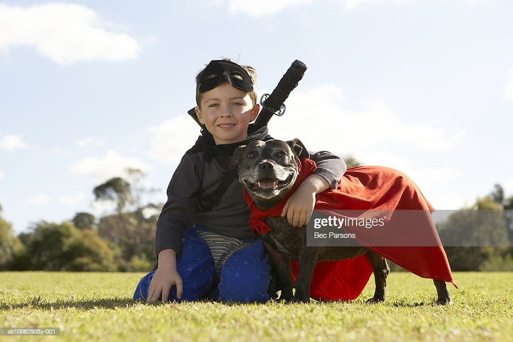Boy (6-7) wearing costume, sitting with dog in park (surface level), portrait : Stock Photo