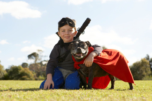 Boy (6-7) wearing costume, sitting with dog in park (surface level), portrait