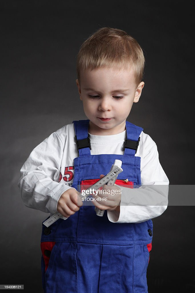 Boy wearing coveralls holding folding rule : Stock Photo