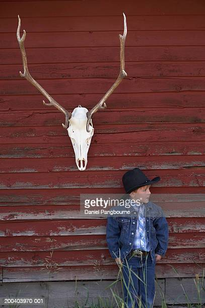 Boy (5-7) wearing cowboy hat, standing by deer skull hanging on wall