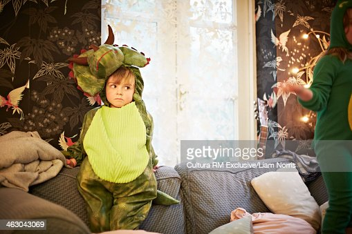 Boy wearing dinosaur outfit in living room : Stock Photo