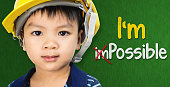 Boy wearing engineering hat with Im possible text for Educational and occupation possibility concept