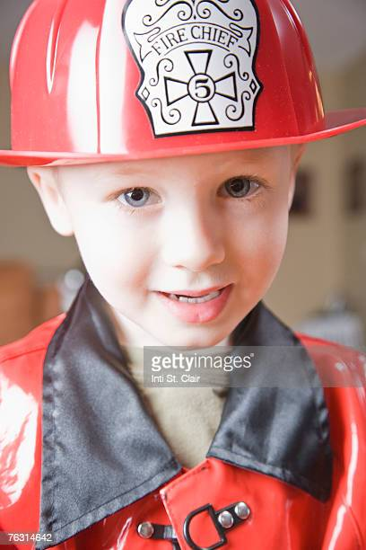 Boy (3-4) wearing firefighter's costume, portrait, close-up