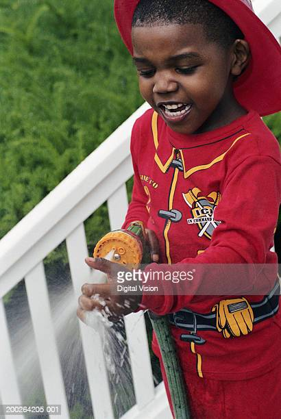 Boy (3-5) wearing fireman costume, holding hose