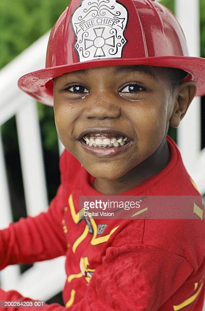 Boy (3-5) wearing fireman costume, smiling, portrait