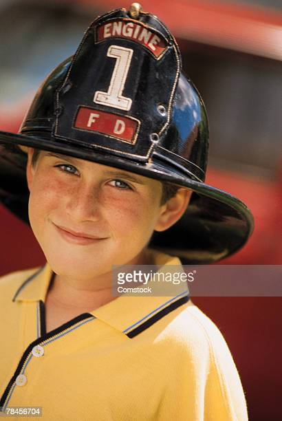 Boy wearing fireman's helmet