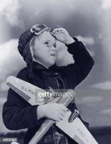 Boy (8-10) wearing flying cap and goggles holding toy plane (B&W) : ストックフォト