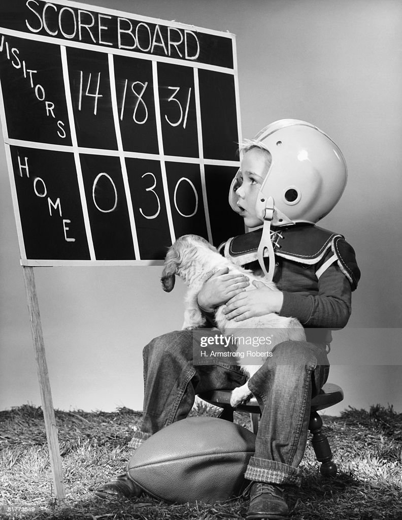 Boy wearing football helmet and pads, holding puppy and ball, looking at scoreboard. : Photo