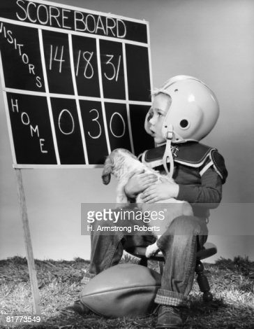 Boy wearing football helmet and pads, holding puppy and ball, looking at scoreboard. : Foto de stock