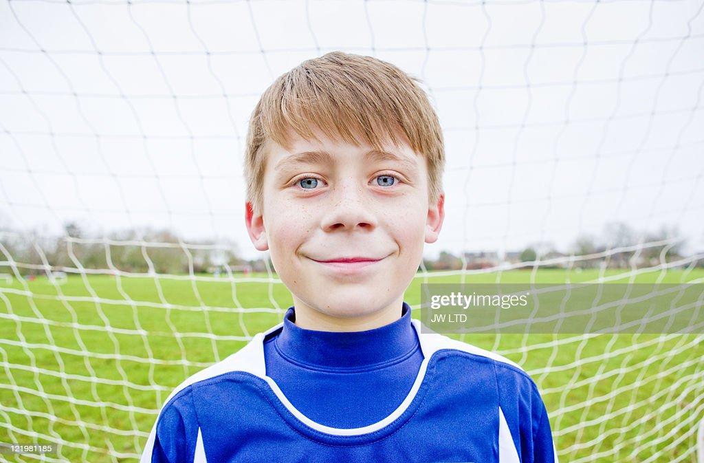 Boy wearing football shirt in goal, portrait : Stock Photo