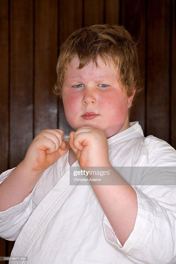 Boy (6-8) wearing gi, in Tae Kwan Do stance, portrait, close-up : Stock Photo