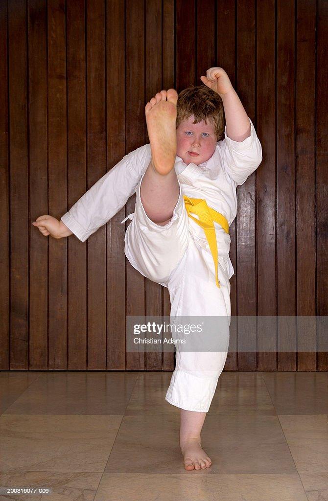 Boy (6-8) wearing gi, performing kick, portrait : Stock Photo
