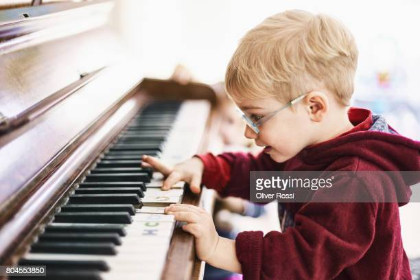 Boy wearing glasses playing piano
