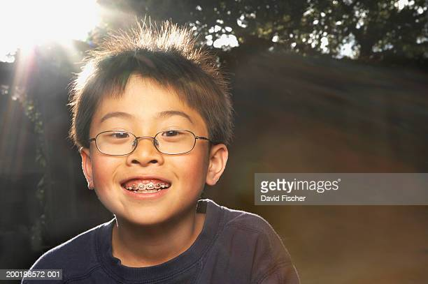 Boy (7-9) wearing glasses, smiling, portrait