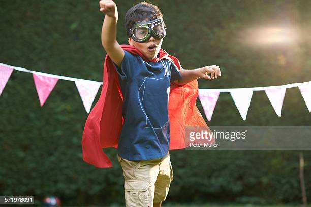 Boy wearing goggles and cape in superhero stance