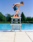 Boy (8-9) wearing goggles and flippers on starting block at swimming pool