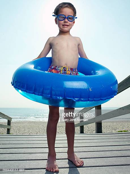 Boy (5-7) wearing goggles with float on boardwalk, portrait