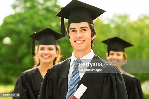 Boy Wearing Graduation Gown And Mortar Board At College Stock ...