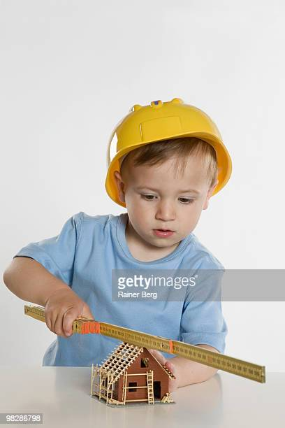 Boy (2-3) wearing hard hat, playing with folding ruler