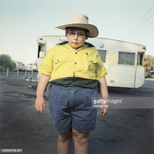Boy (6-8) wearing hat, standing by caravan, portrait