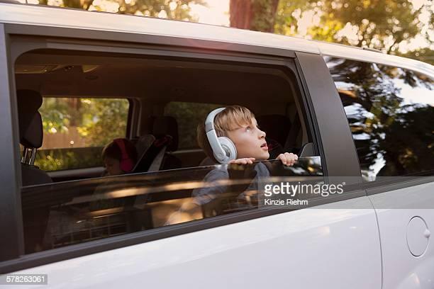 Boy wearing headphones gazing out of car window