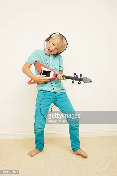 Boy wearing headphones playing guitar