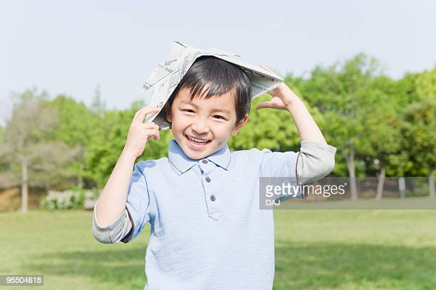 Boy Wearing Headpiece Made of Newspaper