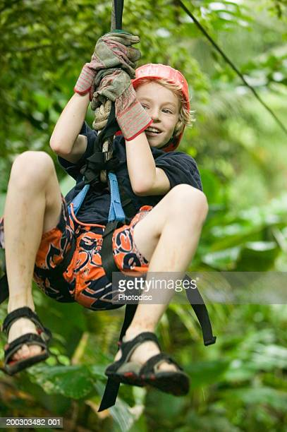 Boy (8-9) wearing helmet hanging on rope in forest
