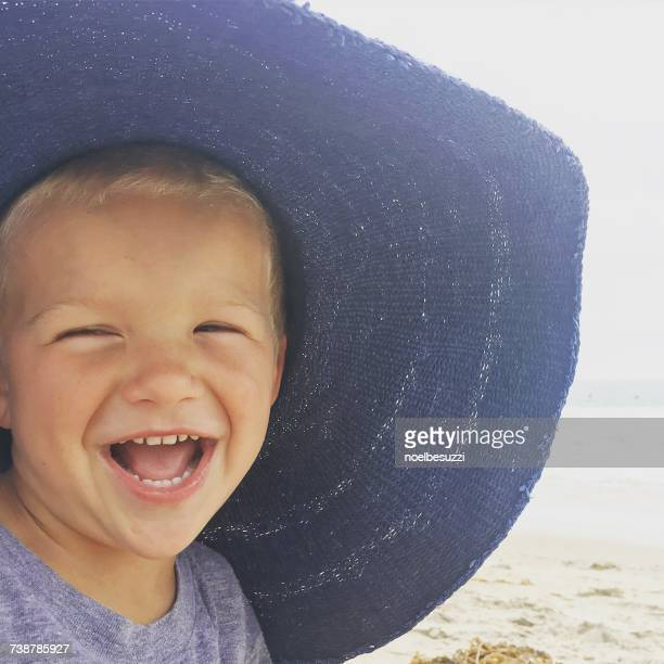 Boy wearing his mothers beach hat laughing