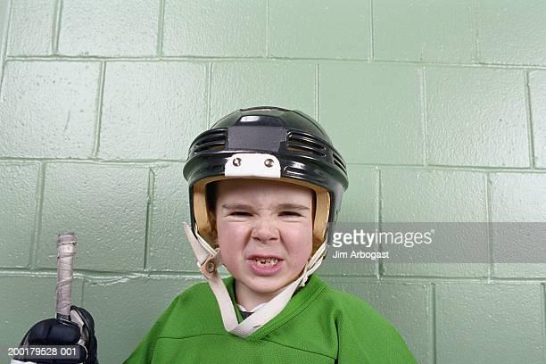 Boy (4-6) wearing ice hockey helmet, making face, portrait