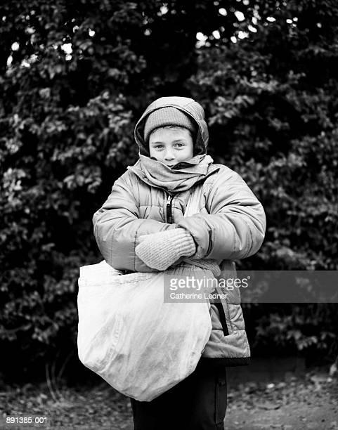 Boy (10-12) wearing jacket, holding sack of newspapers (B&W)