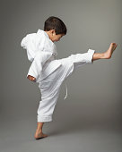 Boy (4-6) wearing karate outfit, kicking leg