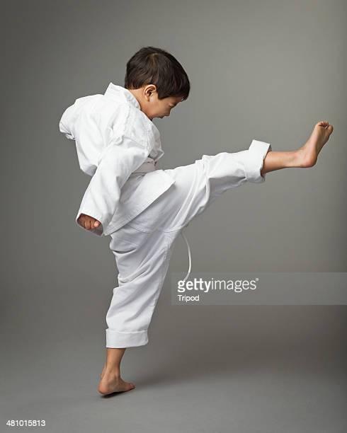 Boy (4-6) wearing karate outfit, kicking leg