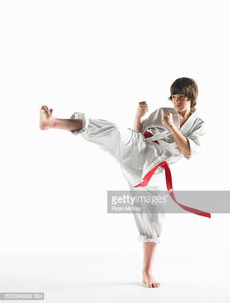 Boy (12-14) wearing karate uniform, preforming karate kick