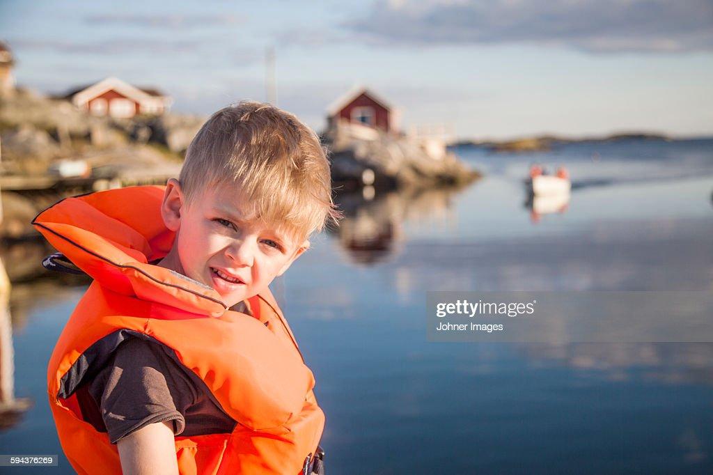 Boy wearing life jacket looking at camera