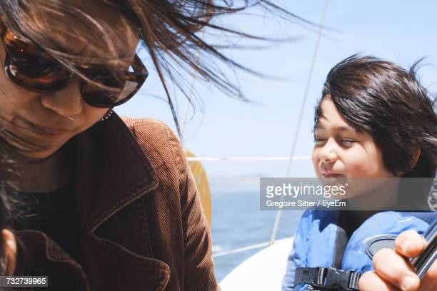 Boy Wearing Life Jacket While Traveling In Sailboat With Parents