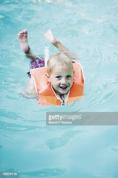Boy wearing life vest learning how to swim