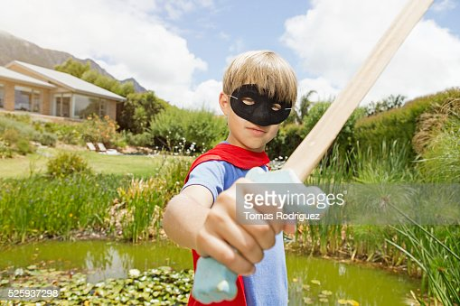 Boy (6-7) wearing mask and holding wooden sword : Foto de stock