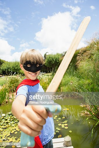 Boy (6-7) wearing mask and holding wooden sword : Stock-Foto