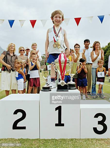 Boy (4-6) wearing medals standing on winners podium with trophies