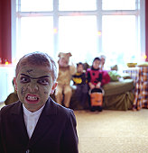 Boy (6-8) wearing monster costume, making a face, portrait