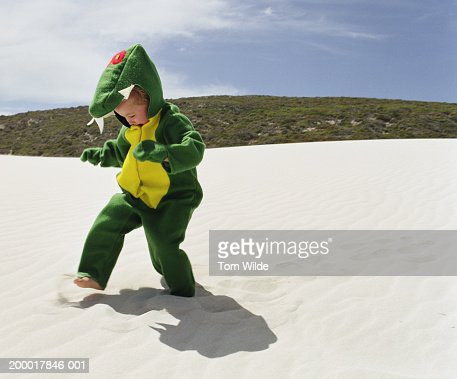 Boy (2-4) wearing monster outfit on beach : Stock Photo
