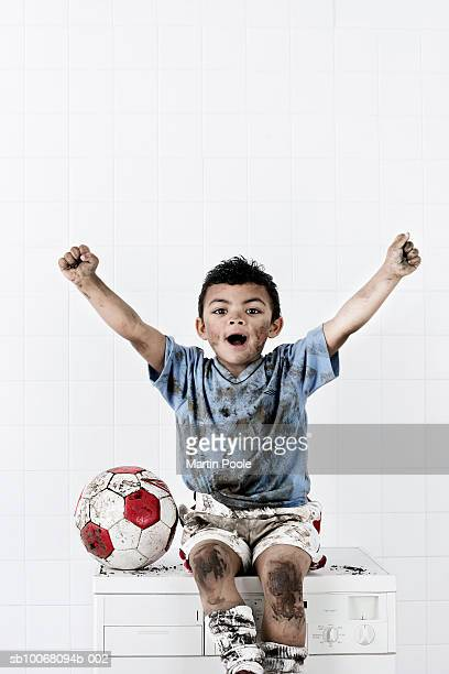 Boy (2-3) wearing muddy soccer kit, celebrating on washing machine