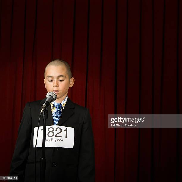 Boy wearing number and speaking on stage