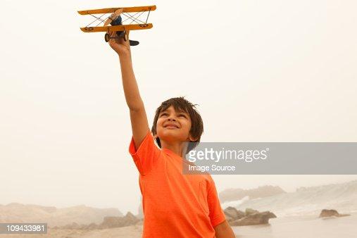 Boy wearing orange t shirt playing with toy plane