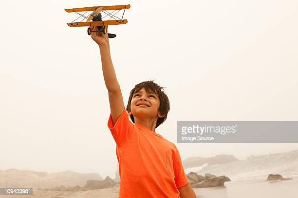 Boy wearing orange t shirt playing with toy plane