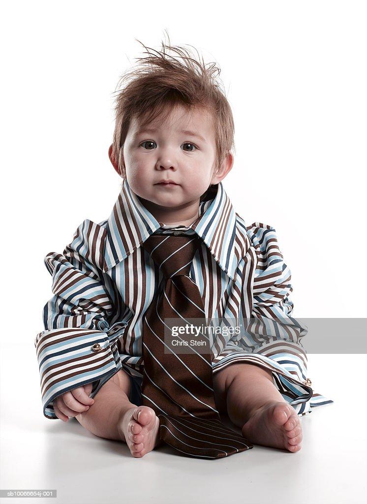 Boy (2-3) wearing oversized shirt and tie, portrait