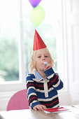 Boy wearing party hat  blowing party horn blower