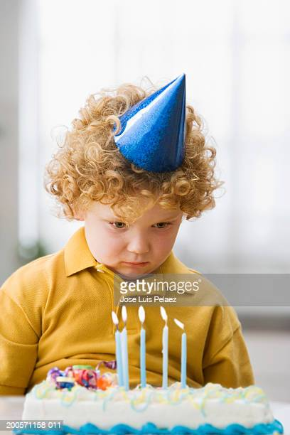 Boy (4-5) wearing party hat, looking at birthday cake, close-up